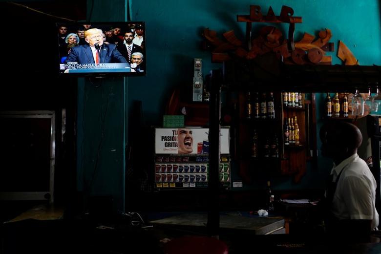 U.S. President Donald Trump is seen on a TV screen announcing his Cuba policy in a state-run bar in Havana, Cuba, June 16, 2017. REUTERS/Alexandre Meneghini