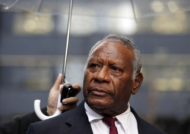 FILE PHOTO: Vanuatu's President Baldwin Lonsdale, standing under an umbrella, listens to a question during an interview with Reuters, after attending the third United Nations World Conference on Disaster Risk Reduction (WCDRR), in Tokyo, March 16, 2015, before leaving to return home. REUTERS/Issei Kato/Files