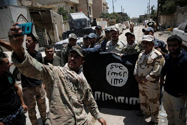 Members of the Iraqi Army's 9th Armoured Division are photographed with an Islamic State flag, claimed after fighting with Islamic State militants in western Mosul, Iraq June 17, 2017. REUTERS/Alkis Konstantinidis      TPX IMAGES OF THE DAY