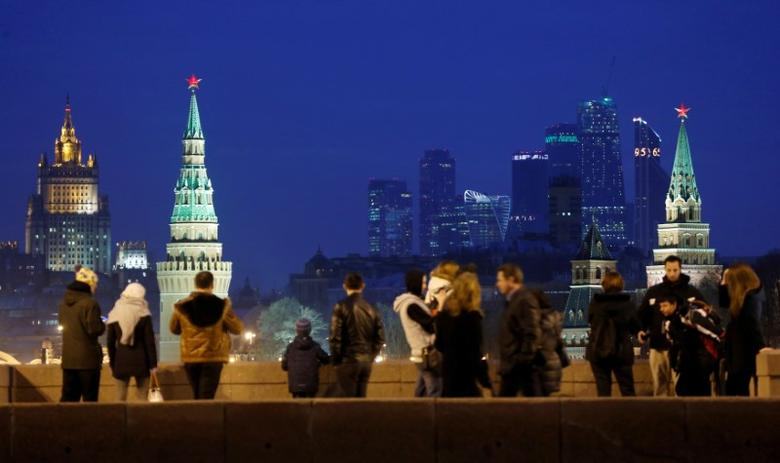 FILE PHOTO: People stand on the Great Moskvoretsky Bridge, with the headquarters of Russian Foreign Ministry seen in the background, in central Moscow, Russia, March 28, 2016. REUTERS/Maxim Shemetov/File Photo