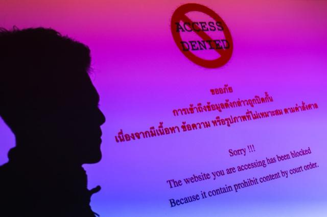 A man is silhouetted onto an electronic screen displaying prohibited website in Bangkok, Thailand, in this June 19, 2017 illustration photo. REUTERS/Athit Perawongmetha/Illustration