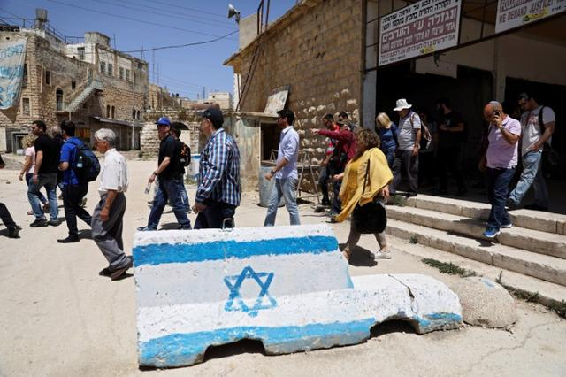Visitors on a tour held by far-right group ''Im Tirzu'' walk on a street in the West Bank city of Hebron May 8, 2017. Picture taken May 8, 2017. REUTERS/Ronen Zvulun
