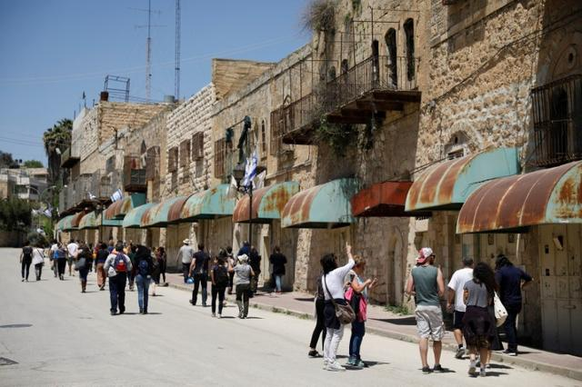 Visitors on a tour held by leftwing NGO ''Breaking the Silence'' walk down Shuhada street in the West Bank city of Hebron April 19, 2017. Picture taken April 19, 2017.REUTERS/Amir Cohen