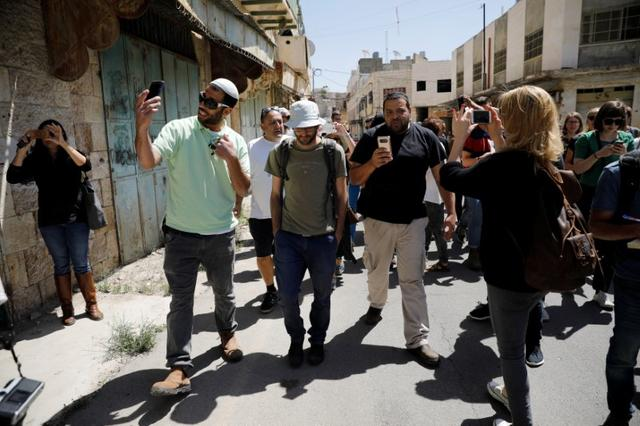 Israeli settlers ( 2ndL and 4thL) use their mobile phones as they disrupt a tour held by leftwing NGO ''Breaking the Silence'', as they walk down a street in the West Bank city of Hebron April 19, 2017. Picture taken April 19, 2017.REUTERS/Amir Cohen
