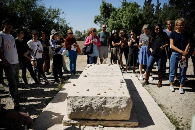Visitors on a tour held by leftwing NGO ''Breaking the Silence'', gather around the grave of Baruch Goldstein, an Israeli settler, who shot dead 29 Palestinians inside Hebron's Al Ibrahimi Mosque, in 1994, in the West Bank city of Hebron April 19, 2017. Picture taken April 19, 2017.REUTERS/Amir Cohen
