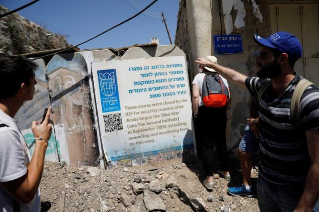 Visitors on a tour held by leftwing NGO ''Breaking the Silence'' stand next to a sign in the West Bank city of Hebron April 19, 2017. Picture taken April 19, 2017.REUTERS/Amir Cohen