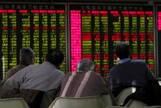 Imagen de archivo de hombres mirando un tablero electrónico que contiene información de los mercados chinos, en Pekín, China. 5 de enero 2016. Las acciones chinas subieron el lunes y el índice CSI300 cortó una racha de tres días de pérdidas, por señales de que la restricción de liquidez está disminuyendo y en momentos en que se esperan menos salidas a bolsa en el mercado. REUTERS/Kim Kyung-Hoon/File Photo