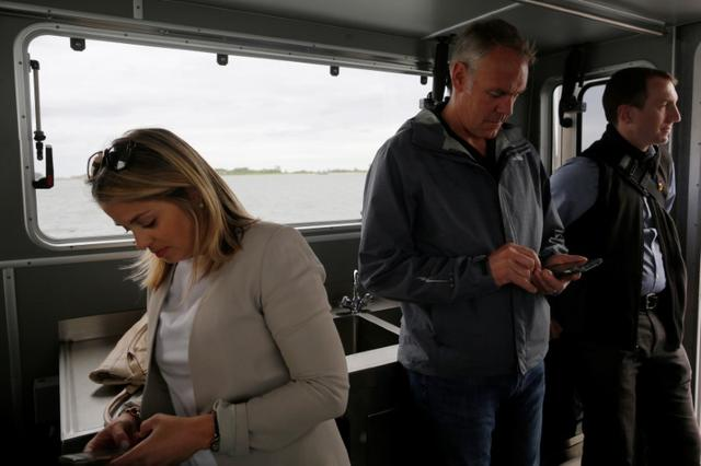 U.S. Interior Secretary Ryan Zinke (C) checks his mobile phone after a visit to Georges Island, part of his National Monuments review process, in Boston Harbor, Massachusetts, U.S., June 16, 2017.   REUTERS/Brian Snyder