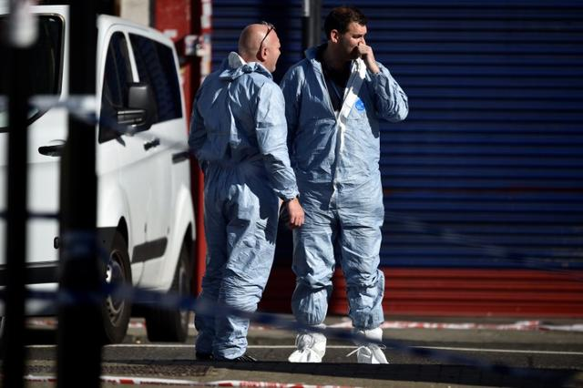 Forensic investigators stand behind cordon tape at the scene of an attack where a man drove a van at Muslim worshippers outside a mosque in Finsbury Park in North London, Britain, June 19, 2017. REUTERS/Hannah McKay