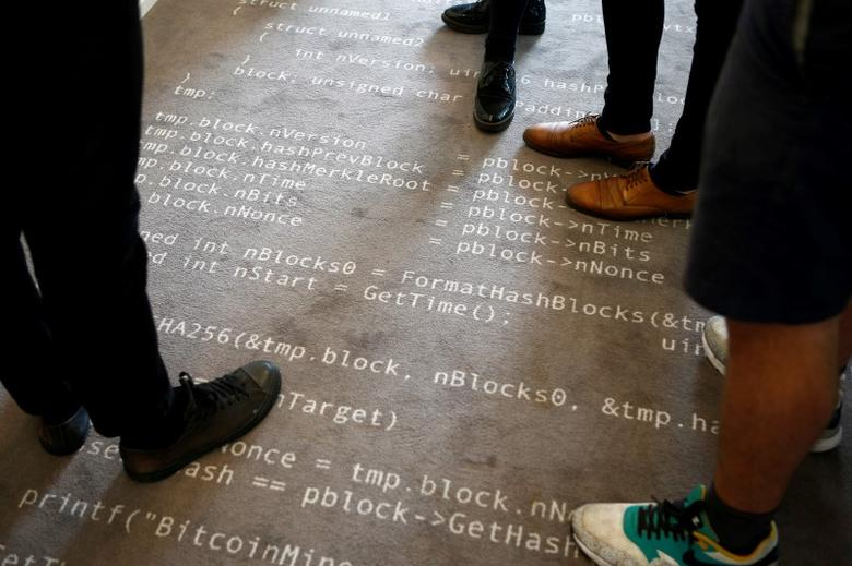 Employees of the Fintech N26 (Number26), stand on a carpet with the Bitcoin source code printed on it in Berlin, Germany, August 19, 2016.    REUTERS/Axel Schmidt