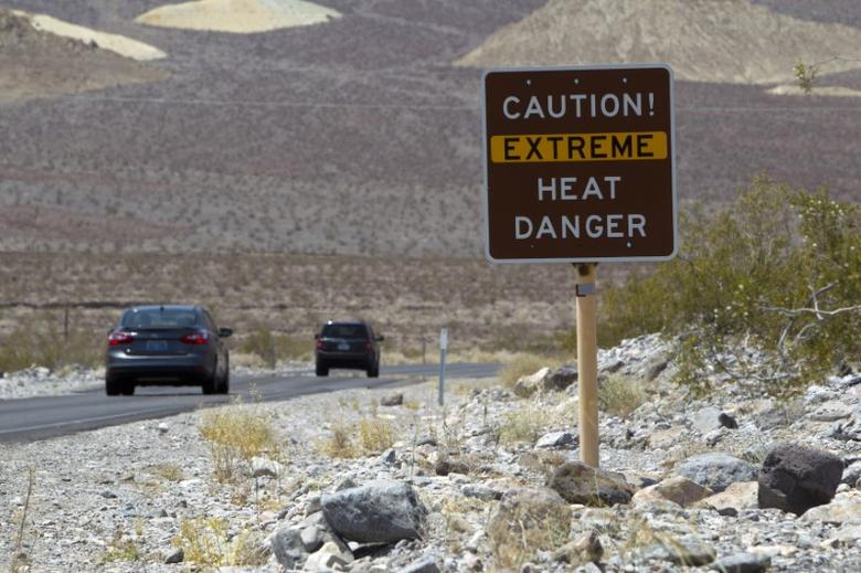 FILE PHOTO - A sign warns of extreme heat as tourists enter Death Valley National Park in California June 29, 2013. REUTERS/Steve Marcus