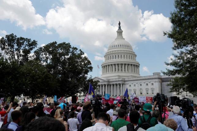 6月21日、米共和党が成立を目指す医療保険制度改革(オバマケア)代替法案について、低所得者や既往歴のある人に不利になると国民の過半数が考えていることがロイター/イプソスが21日に公表した世論調査で明らかになった。写真はオバマケア代替法案の反対デモに参加する人々。ワシントンで撮影(2017年 ロイター/AARON P. BERNSTEIN)