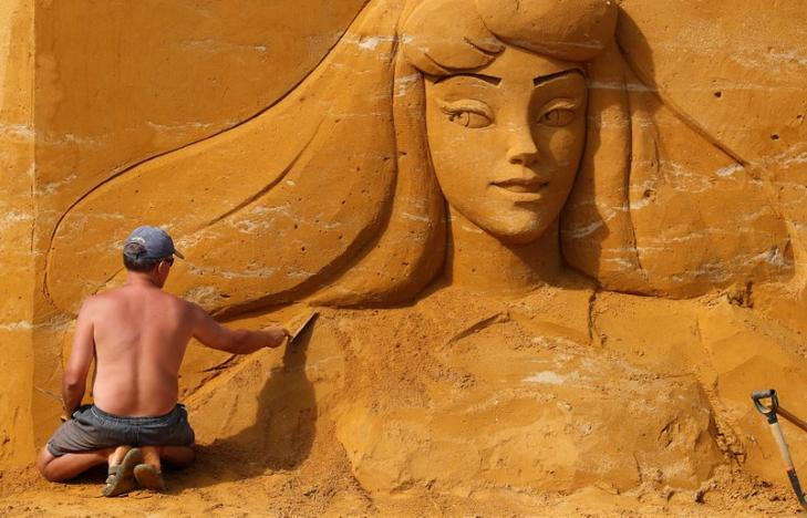 An artist works on a sculpture during the Sand Sculpture Festival 'Disney Sand Magic' in Ostend, Belgium June 22, 2017. Yves Herman