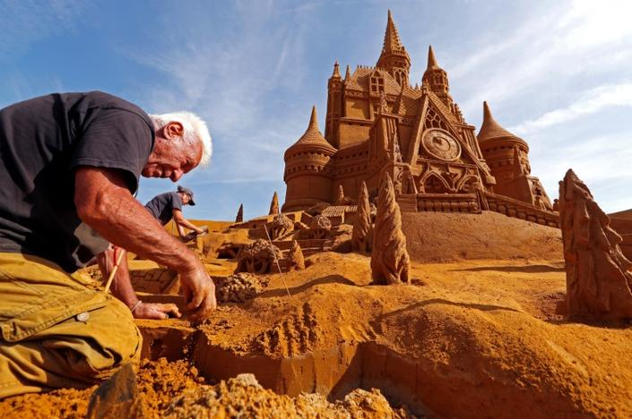 Sand carver Franco Daga from Italy works on a sculpture during the Sand Sculpture Festival 'Disney Sand Magic' in Ostend, Belgium June 22, 2017. Yves Herman