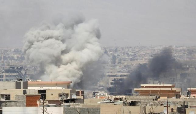 6月26日、イラク軍は過激派組織「イスラム国」(IS)からイラク北部の主要都市モスルを奪還する作戦が数日中に終了するとの見通しを示した。写真はイラク軍の空爆を受けて煙が立ち上るモスルの旧市街。25日撮影(2017年 ロイター/Erik De Castro)