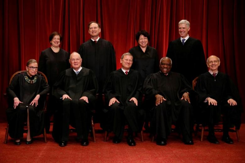 U.S. Chief Justice John Roberts (seated C) leads Justice Ruth Bader Ginsburg (front row, L-R), Justice Anthony Kennedy, Justice Clarence Thomas, Justice Stephen Breyer, Justice Elena Kagan (back row, L-R), Justice Samuel Alito, Justice Sonia Sotomayor, and Associate Justice... Jonathan Ernst