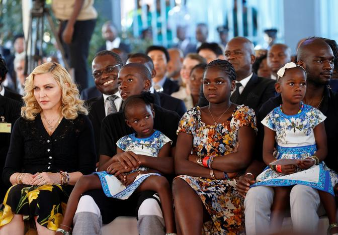 US pop star Madonna (L) sits with her adopted children during the opening of Mercy James hospital in Blantyre, Malawi, July 11,2017. Siphiwe Sibeko