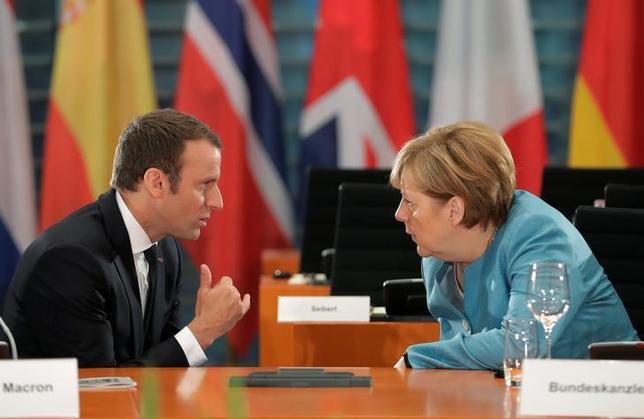 7月13日、マクロン仏大統領(写真左)は地方紙「ウエスト・フランス」に掲載されたインタビュー記事の中で、欧州連合は未完成のプロジェクトであり、ユーロ圏各国の結束をさらに強めるよう求めた。右はメルケル独首相、ベルリンで6月代表撮影(2017年 ロイター/Markus Schreiber)