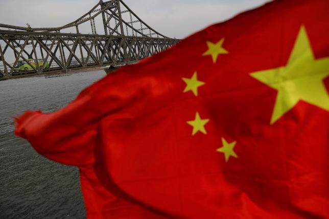 7月14日、格付け会社フィッチ・レーティングスは、中国の格付けを「Aプラス」に据え置いた。見通しは「安定的」とした。写真は4月、中国遼寧省の丹東市にある橋と同国国旗(2017年 ロイター/Damir Sagolj)