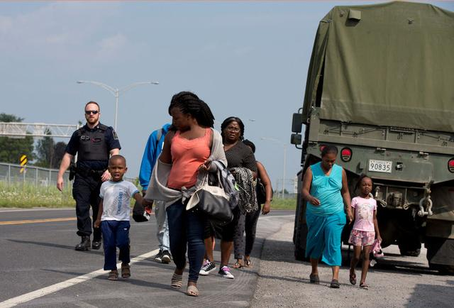 A group of asylum seekers walk down the street as they are escorted from their tent encampment to be processed at Canada Border Services in Lacolle, Quebec, Canada August 11, 2017. REUTERS/Christinne Muschi