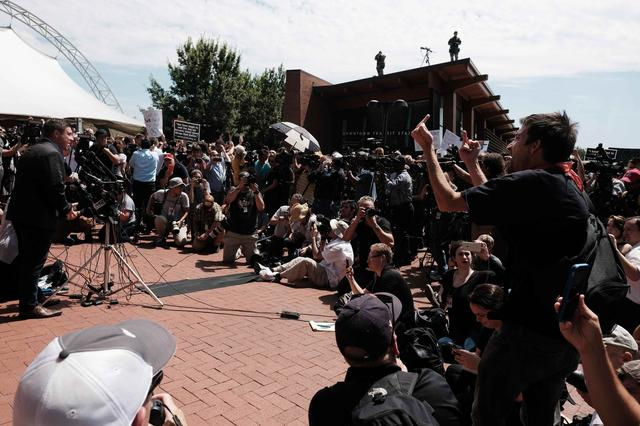 Unite The Right rally organizer Jason Kessler (L) attempts to speak at a press conference in front of Charlottesville City Hall in Charlottesville, Virginia, U.S. August 13, 2017. Kessler was heckled and later chased away by people in the crowd, and eventually took refuge in the Charlottesville Police Department.  REUTERS/Justin Ide