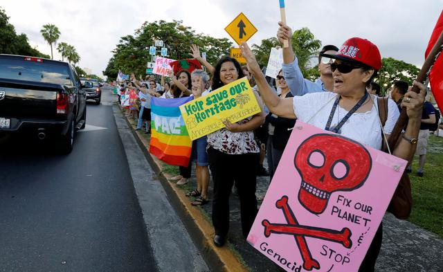 Local residents display placards and chant slogans during a peace rally at Chief Quipuha Park, on the island of Guam, a U.S. Pacific Territory, August 14, 2017. REUTERS/Erik De Castro