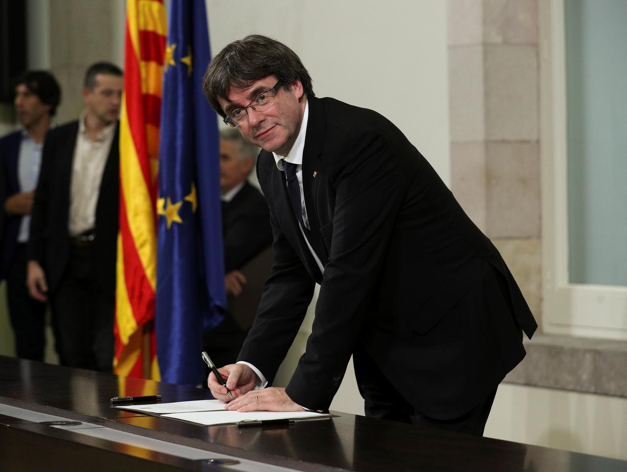 Thủ lĩnh xứ Catalonia Carles Puigdemont ký tuyên bố về chủ quyền toàn vẹn tại nghị viện Catalonia. Ảnh: REUTERS