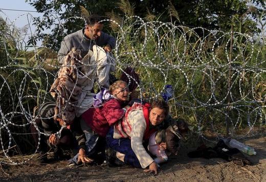 Syrian migrants cross under a fence into Hungary at the border with Serbia, near Roszke, August 27, 2015. Bernadette Szabo: Rail... BERNADETT SZABO Thu Dec 07 13:05:39 UTC 2017