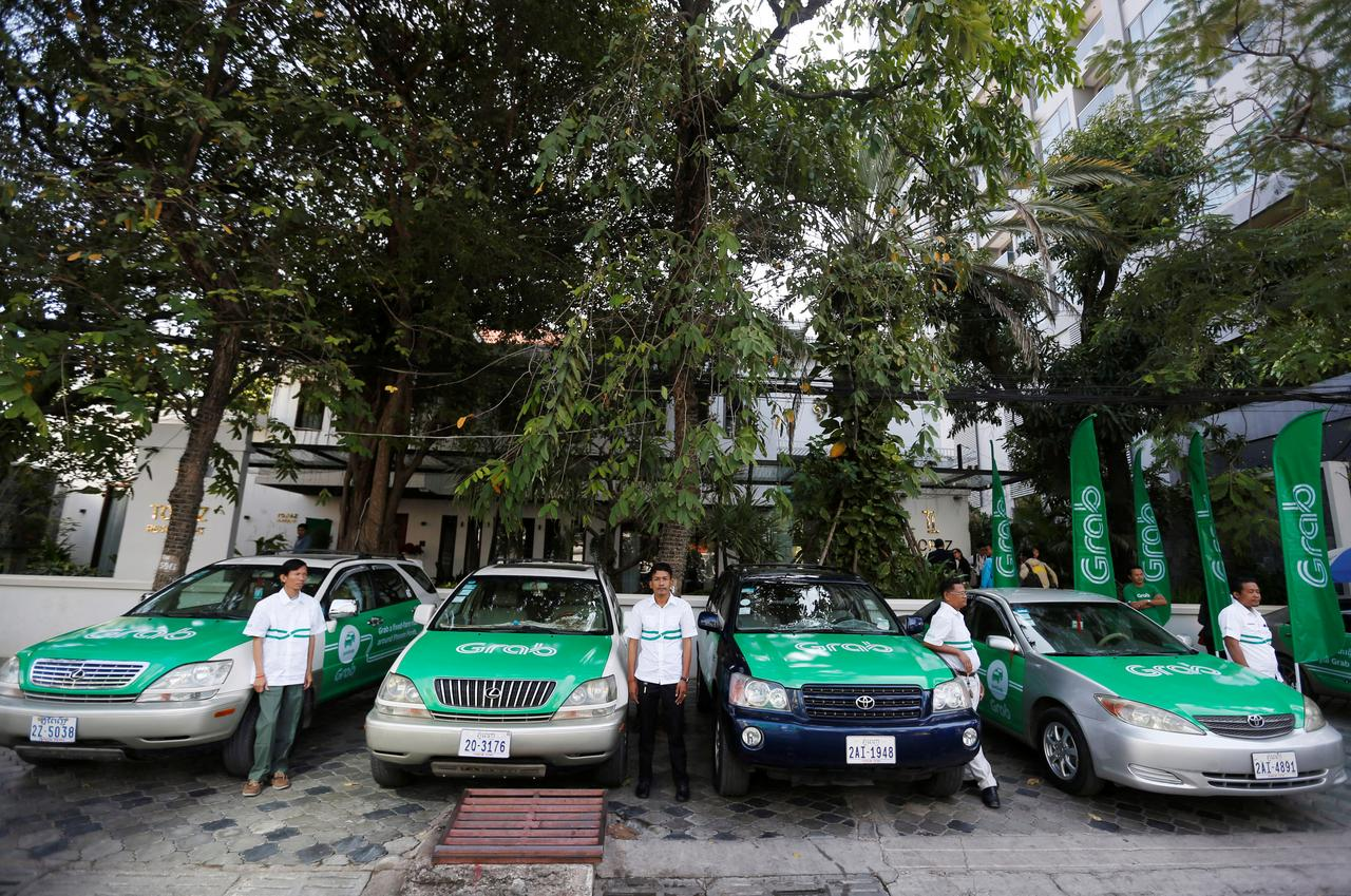 Drivers stand near Grab cars during a launch ceremony in Phnom Penh, Cambodia on Dec 19, last year | Reuters.com