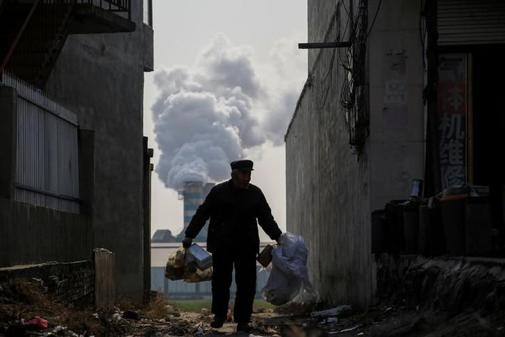 A man collects recyclables from an alley as smoke billows from the chimney of a factory near Shijiazhuang, Hebei province, China, December 7, 2017. Thomas Peter