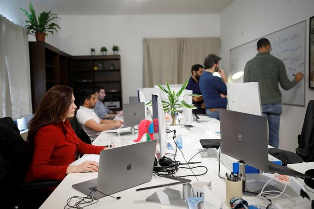 Employees of the D-ID startup company work at the company's office in Tel Aviv, Israel February 7, 2018. REUTERS/Amir Cohen
