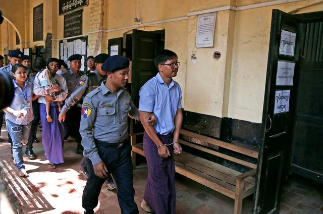 Detained Reuters journalist Wa Lone and Kyaw Soe Oo are escorted by police while arriving for a court hearing after lunch break in Yangon, Myanmar February 14, 2018. REUTERS/Stringer