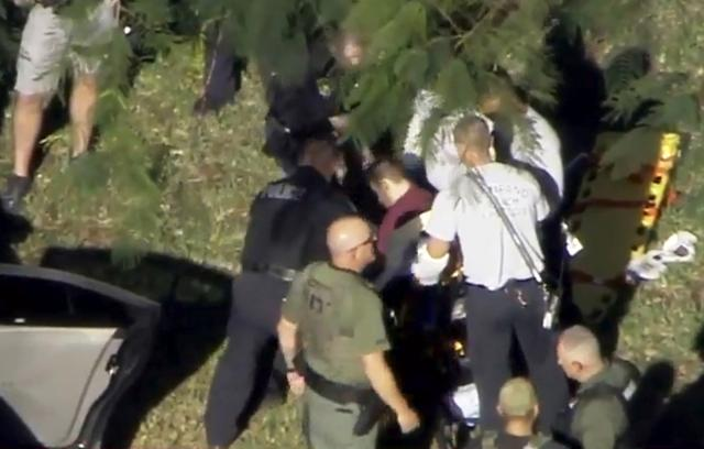 A man placed in handcuffs by police is loaded onto a stretcher near Marjory Stoneman Douglas High School following a shooting incident in Parkland, Florida, February 14, 2018 in a still image from video. WSVN.com via REUTERS