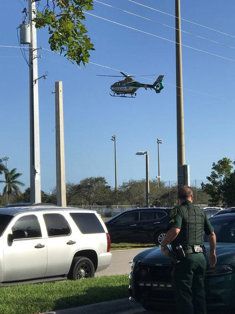 Police cars and a helicopter are seen in Coral Springs after a shooting at the Marjory Stoneman Douglas High School in Parkland, Florida, U.S. February 14, 2018 in this image obtained from social media. CREDIT: TWITTER / @GRUMPYHAUS via REUTERS