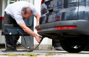 A motor mechanic measures exhaust emissions in a diesel-engined car in...