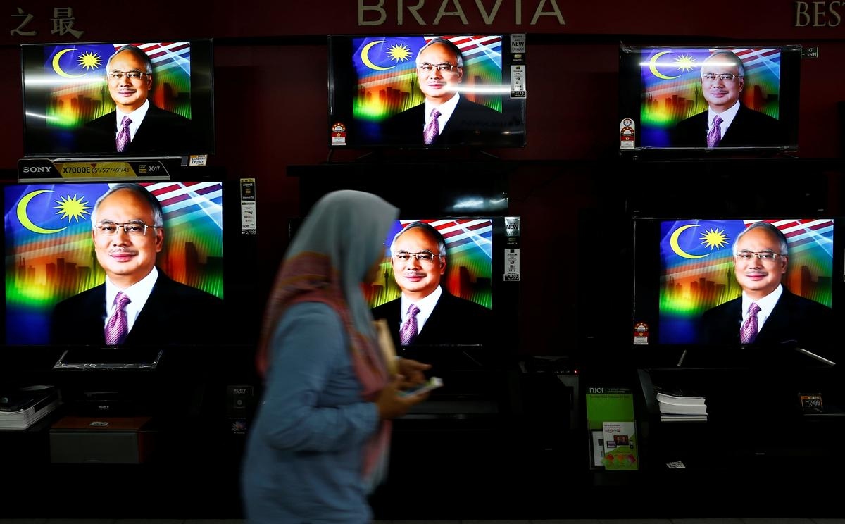 Image result for A woman passes a live telecast of Malaysia's Prime Minister Najib Razak addressing the nation on the dissolution of Parliament at a electronics shop in Port Klang, Malaysia April 6, 2018. REUTERS/Lai Seng Sin