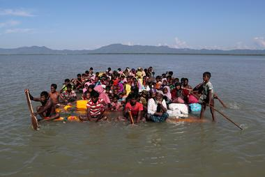 FILE PHOTO: Rohingya refugees cross the Naf River with an improvised raft...