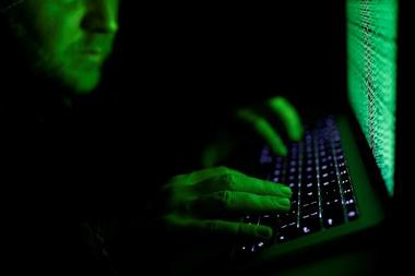 Man types on a computer keyboard in front of the displayed cyber code in...