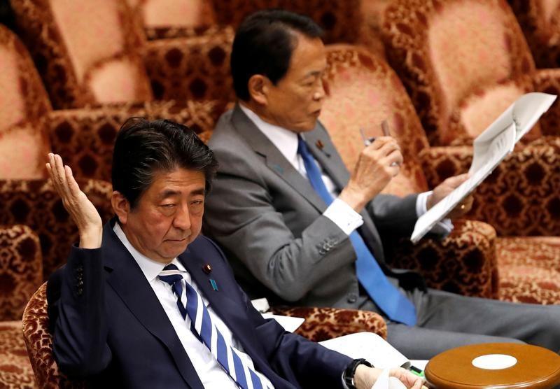 5月28日、安倍晋三首相は、午前の参議院予算委員会で、愛媛県資料で指摘された2015年2月25日前後に加計学園の加計孝太郎理事長とは面会していない、と改めて否定した。写真は3月の参院予算委員会で答弁する安倍首相と麻生財務相(2018年 ロイター/Issei Kato)