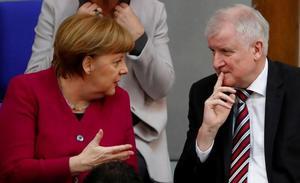 FILE PHOTO: German Chancellor Angela Merkel talks to Interior Minister...