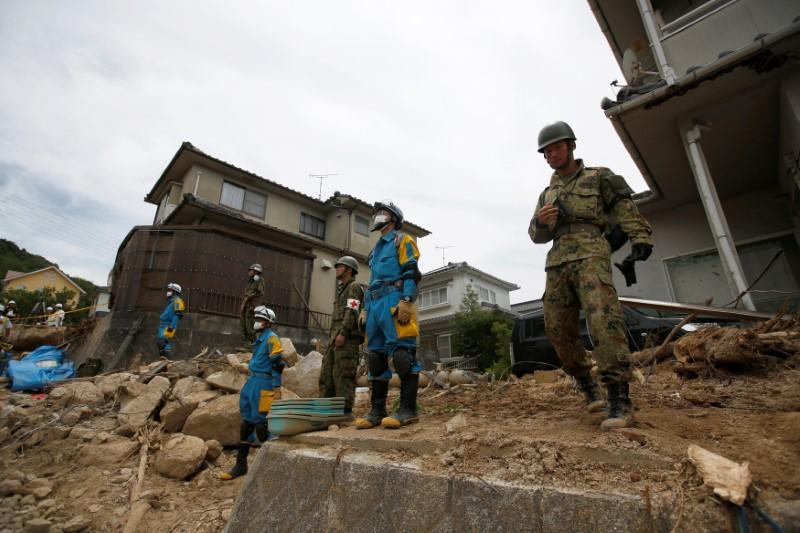 Rescue workers and Japan Self-Defense Force soldiers search for missing people at a landslide site after heavy rain in Kumano Town, Hiroshima Prefecture, western Japan, July 11, 2018. Issei Kato