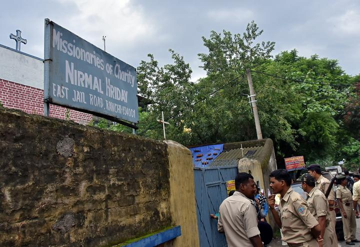 Police stand outside a home which provides shelter for pregnant unmarried...