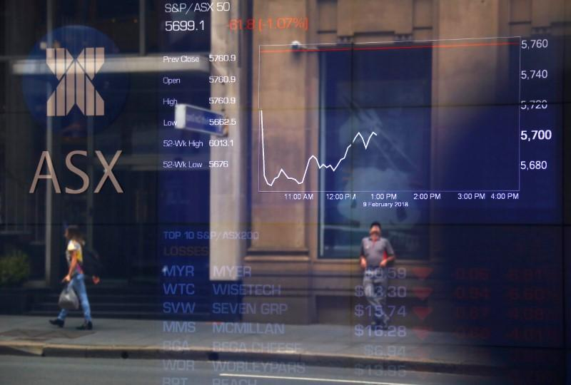 Pedestrians are reflected in a window in front of a board displaying stock prices at the Australian Securities Exchange (ASX) in Sydney, Australia, February 9, 2018.   David Gray