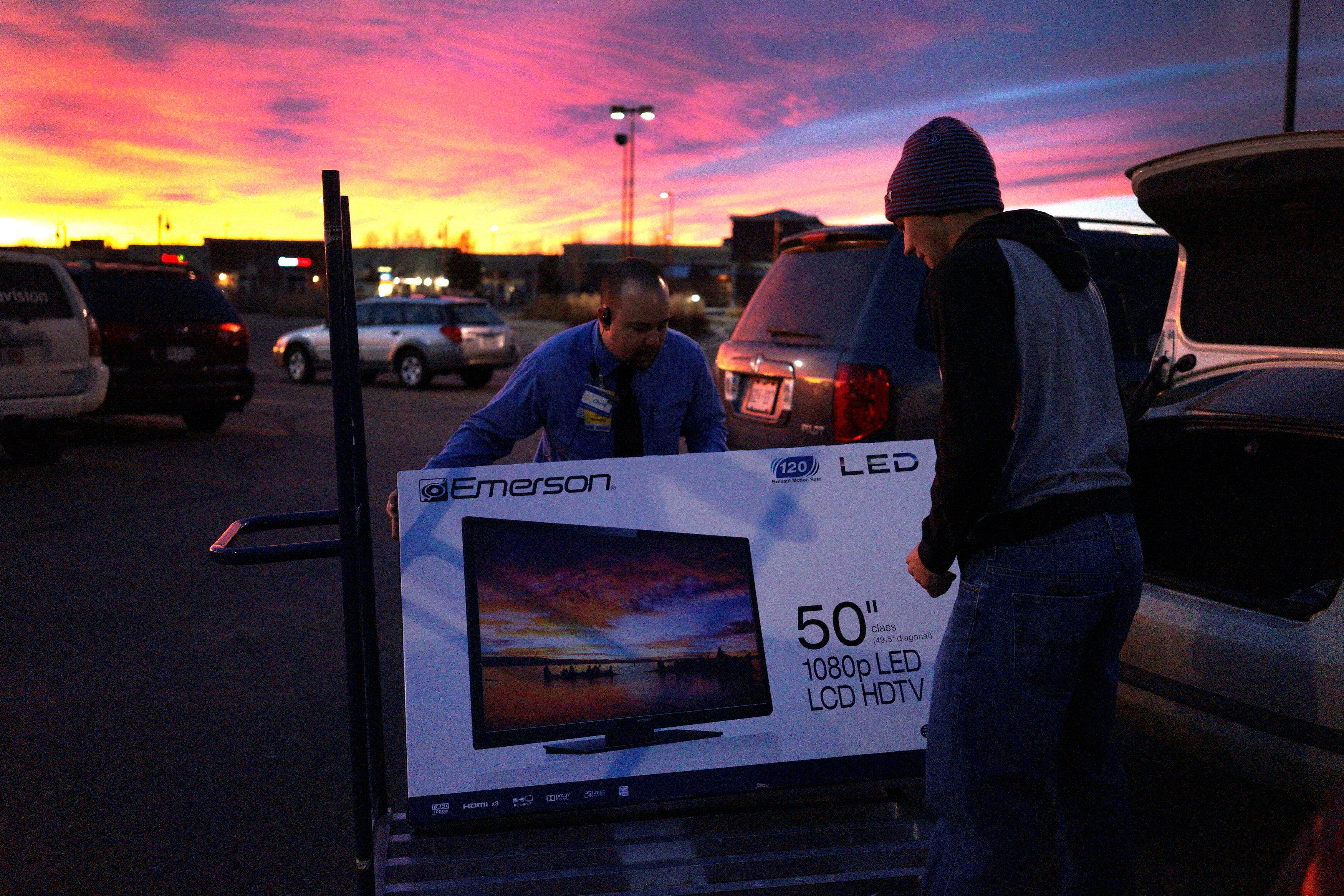 A Walmart employee helps a customer load a 50