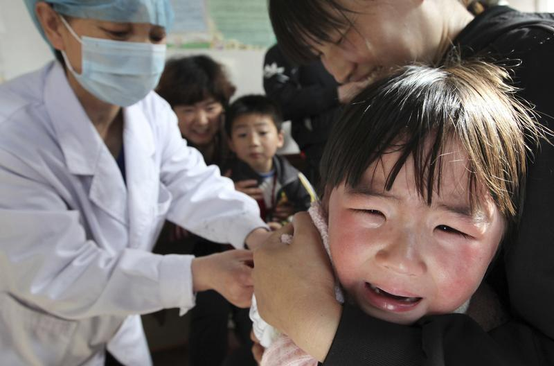 A girl cries in her mother's arm while receiving a vaccination from a nurse at a hospital in Huaibei, Anhui province April 25, 2012. China's Ministry of Health reported Monday that its 2012 budget will amount to 80 billion yuan ($12.69 billion), showing an average of a 13.3 billion yuan ($2.1 billion) increase each year, Xinhua News Agency reported. China Daily
