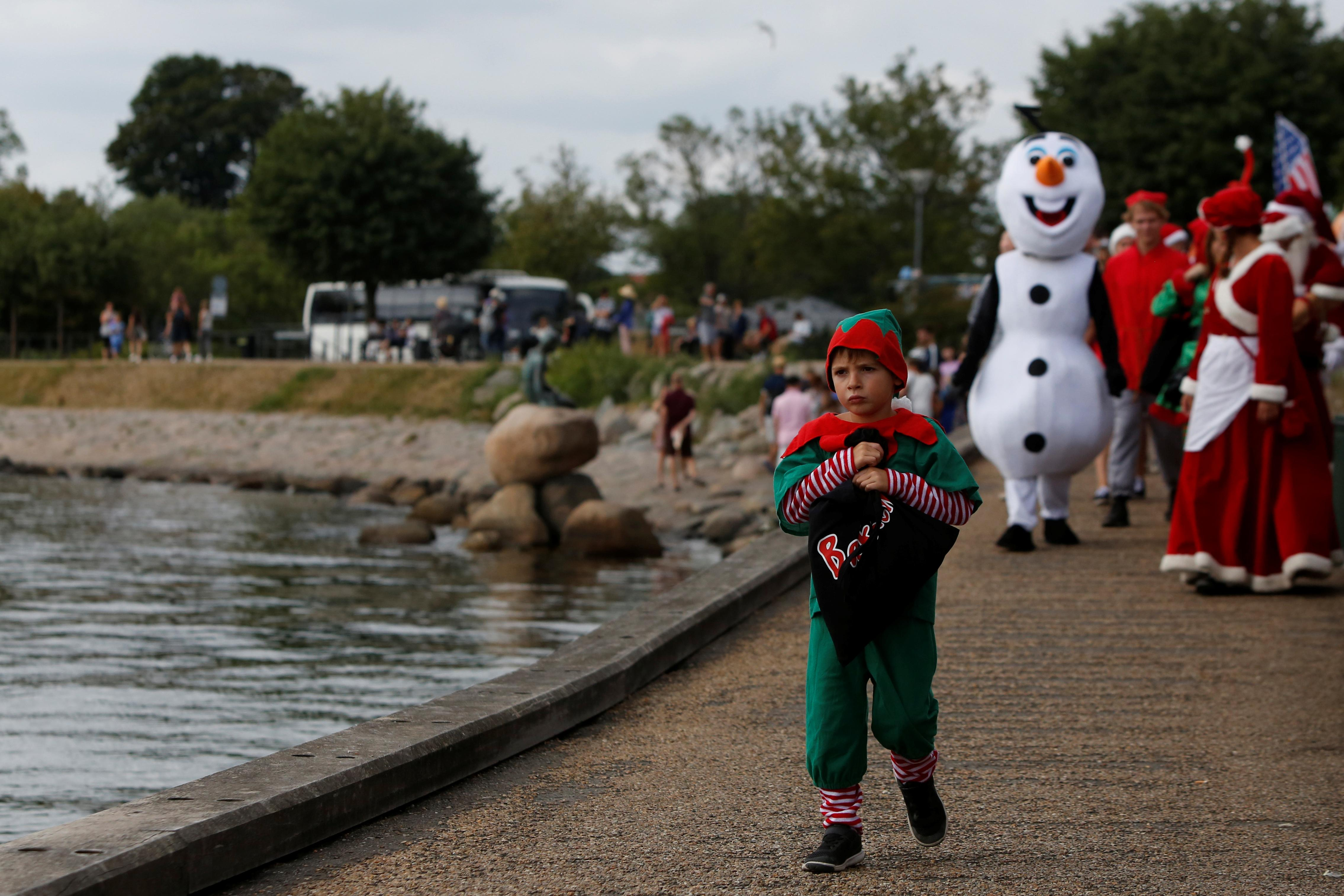 A child dressed as an elf walks along the waterfront during an event in the World Santa Claus Congress, an annual event held every summer in Copenhagen, Denmark, July 23, 2018.  Andrew Kelly