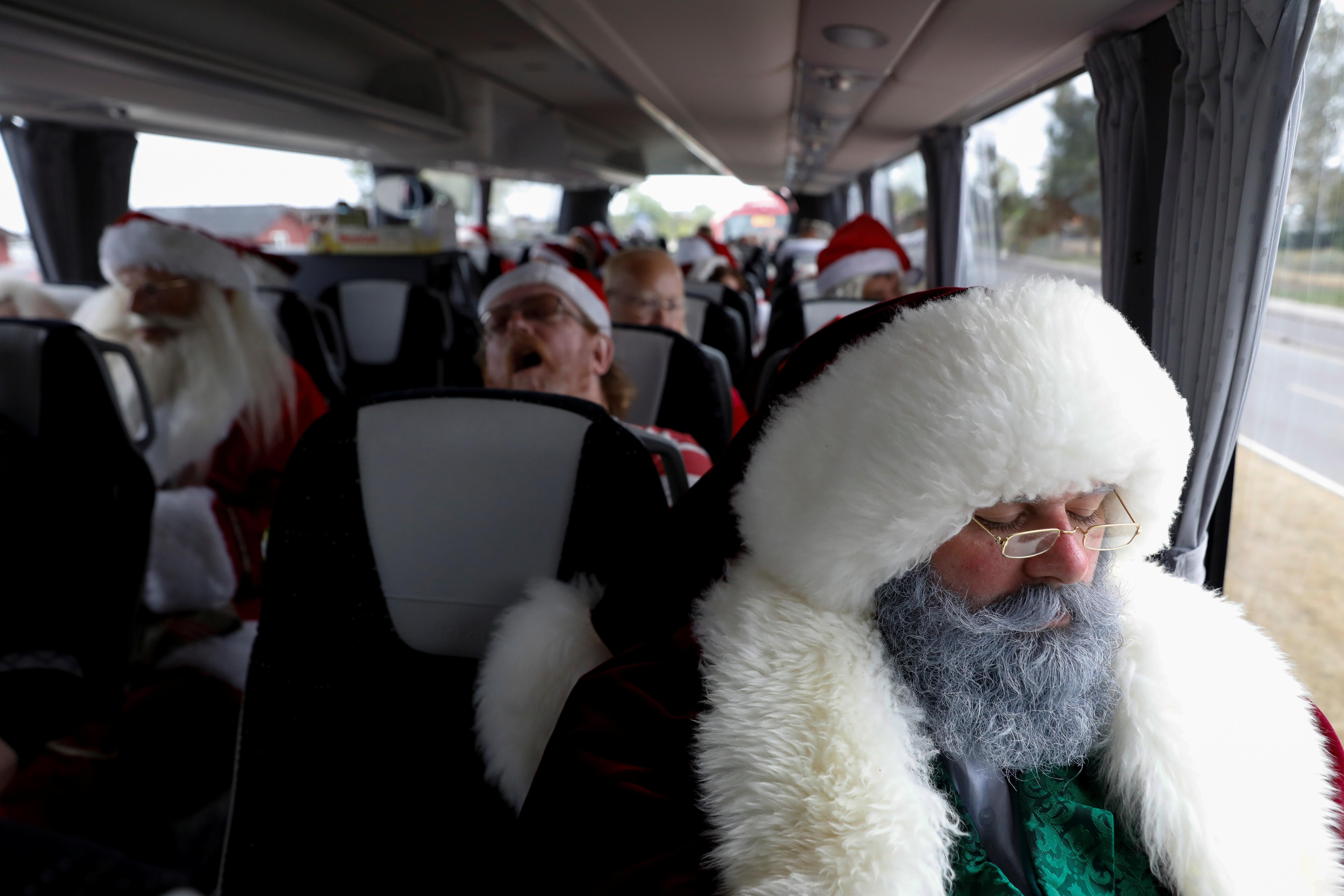 People dressed as Santa Claus rest while on a bus trip between events during the World Santa Claus Congress, an annual event held every summer in Copenhagen, Denmark, July 23, 2018.  Andrew Kelly