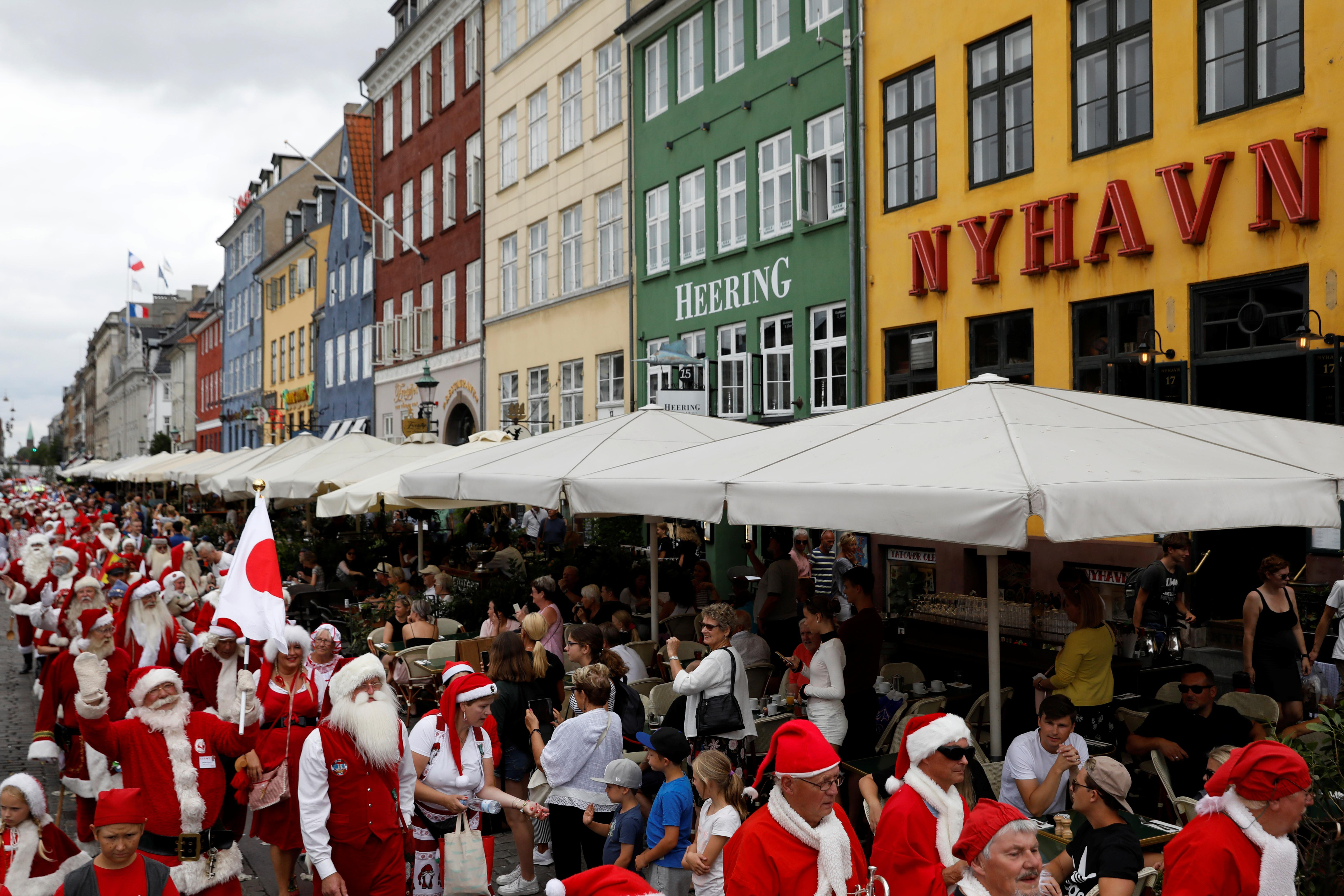 People dressed as Santa Claus walk along Nyhavn as they take part in the World Santa Claus Congress, an annual event held every summer in Copenhagen, Denmark, July 23, 2018.  Andrew Kelly