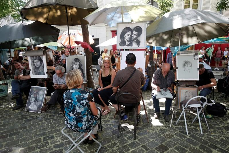 General view of artists who sketch portraits in the street on the