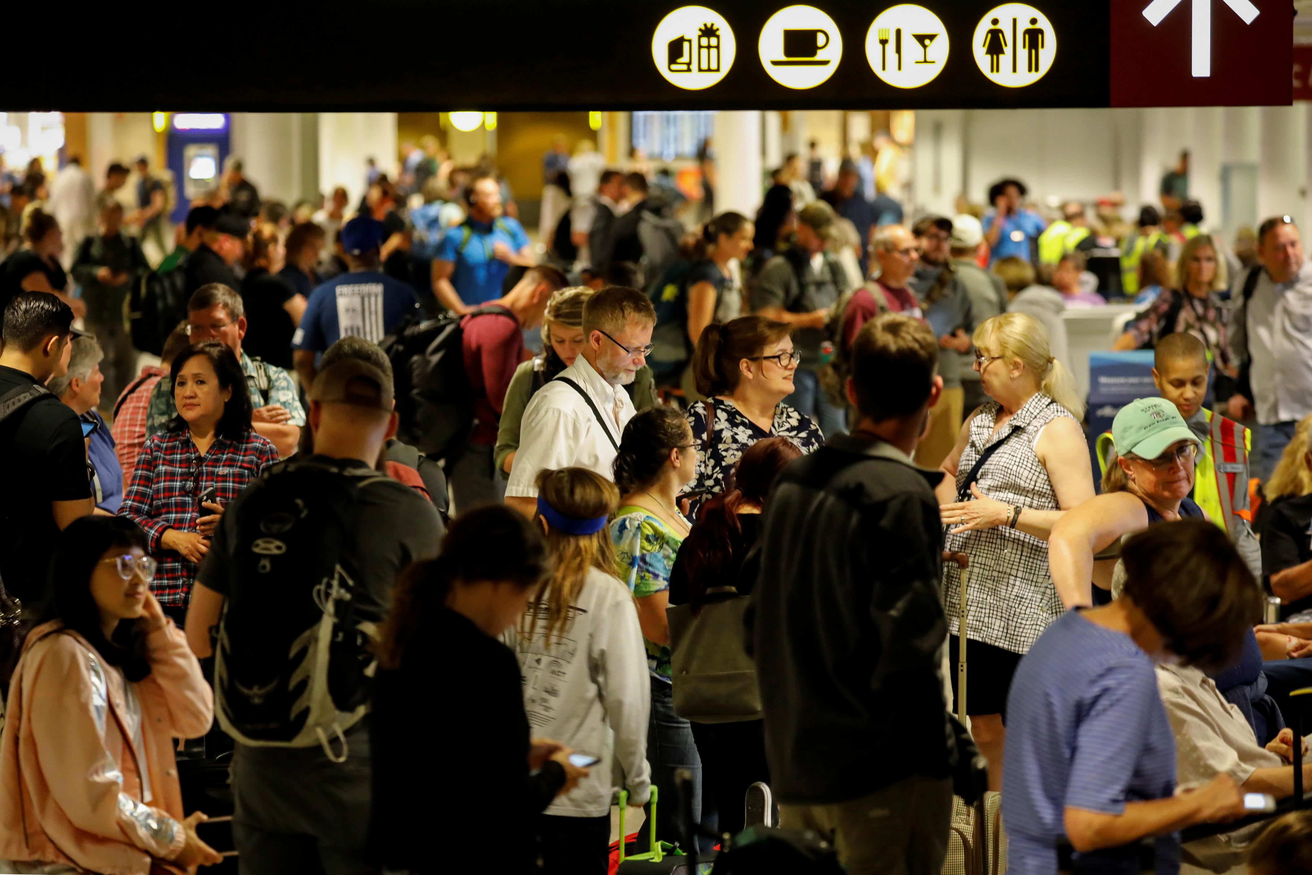 Air Alaska passengers wait in the terminal following an incident where an airline employee took off in an airplane, at Seattle-Tacoma International Airport in Seattle, Washington, U.S., August 10, 2018. Brendan McDermid